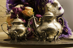 Still Life Old Teaware. Old styled teaware standing on a table sorounded by a vencian mask Stock Images