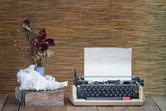 Still life with old typewriter ,book with dry rose flowers. On wooden table stock photo