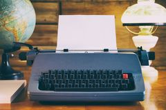 Still life of old typewriter with empty sheet, globe and old fashioned lamp. Retro journalism concept Royalty Free Stock Image