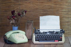 Still life with old typewriter telephone book with dry rose Royalty Free Stock Photo