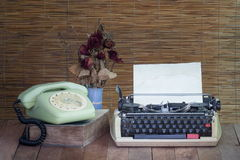 Still life with old typewriter telephone book with dry rose Royalty Free Stock Images