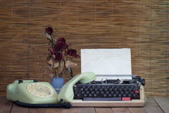 Still life with old typewriter telephone with dry rose flowers. On wooden table royalty free stock photo