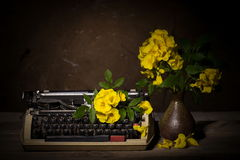 Still life with old typewriter with yellow flowers on wooden Royalty Free Stock Images