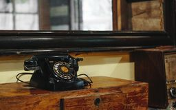 Still life of old vintage retro black telephone on asia style wo. Od table in vintage retro room Stock Photo
