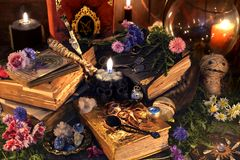 Still life with old witch books, antique lamp, black candles, voodoo doll and ritual objects. Mystic background with ritual esoteric objects, occult, fortune stock image