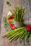 Still life with olive oil asparagus, avocado, pepper and rosemar Stock Photos