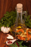 Still life with olive oil, Fusilli Pasta, herbs and spices Royalty Free Stock Image