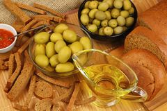 Still life with olive oil, olives and bread Stock Photos