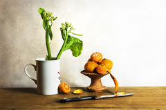 Still life with orange  and flowers. Still life with orange and green flowers on wooden table Royalty Free Stock Photos