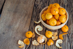 Still life of orange fruit in bowl on old wood background. Royalty Free Stock Images