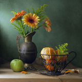 Still life with orange gerbera daisy flowers. And tangerines on wooden table royalty free stock photo