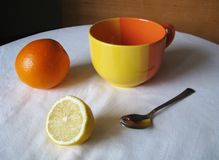 Still life. Orange, lemon, cup and spoon on a white tablecloth. Stock Photo