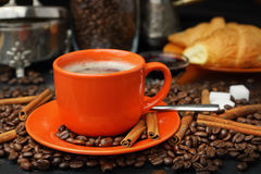 Still life with an orange mug in coffee grains. Still life with coffee grains, sugar, cinnamon, sugar bowl, croissants and an orange cup of coffee Stock Photo