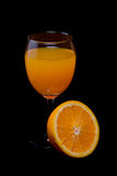 Still life of orange and orange juice in glass on black Royalty Free Stock Photo