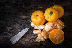 Still life oranges fruit and knife on texture wood. Stock Photos