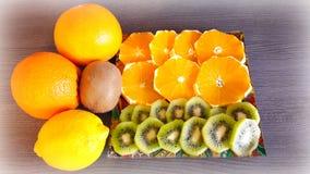 Still life with oranges, lemon and kiwi. Whole oranges, lemon and kiwi fruit and cut fruit on the plate Royalty Free Stock Photography