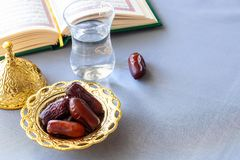 Still life Organic dates, cup of pure drinking water and quran book. Iftar Ramadan concept. Selective focus. Copy space royalty free stock photography