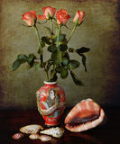 Still life: oriental vase with orange roses and shells on a grun. Vintage still life composition: red japanese vase  with  a bouquet of orange roses and shells Stock Photography