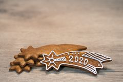 Ornate New Year Bethlehem stars. Still life on wood background. Handmade baked Xmas gingerbread cookie decorated by sugar icing, laid on stacked golden sweets royalty free stock photo