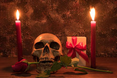 Still life painting photography with human skull, present, rose. And candle on wooden table Royalty Free Stock Images