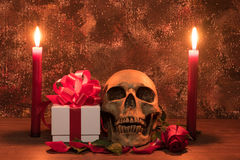 Still life painting photography with human skull, present, rose. And candle on wooden table Royalty Free Stock Photography