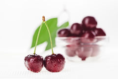 Still life with pair of red cherry and glass bowl Stock Photo