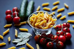 Still life with pasta, cherry tomatoes and cucumbers. stock photo