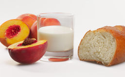 Still Life with Peaches. A glass of milk and bread on a white background Stock Photo