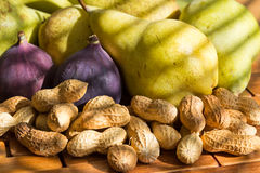 Still life of peanuts, red figs, green pears. Still life of fresh and fragrant peanuts, red figs, green pears at the window with the light trap Stock Images