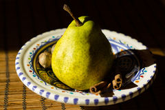 Still life of pear and cinnamon sticks Stock Photo
