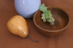 Still life with pear grape and wooden platter royalty free stock photography