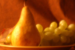 Still Life with Pear and Grapes. A tabletop still life with a pear and green grapes. Softly filtered with a coordinated background stock photography