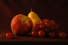 Still life with pear and peach. A fine art still life with peach, pear, and grapes stock image
