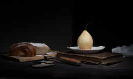 Still life. pears, weet roll, old books on a dark background.  painting, vintage. Stock Photo
