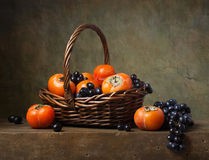 Still life with persimmons and grapes Royalty Free Stock Photos