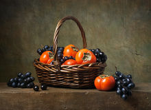 Still life with persimmons and grapes Royalty Free Stock Photography