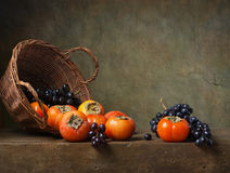 Still life with persimmons and grapes Royalty Free Stock Image