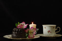 Still life. With peruvian lily, coffee cup, cake an candle royalty free stock images