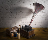 Still life of Phonograph. With three cylinder records on wooden table and white bricks wall Royalty Free Stock Photo