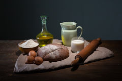 Still life photo of bread and flour with milk and eggs Stock Photography