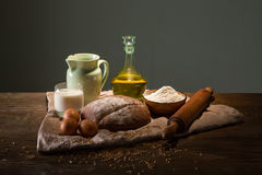 Still life photo of bread and flour with milk and eggs Stock Images