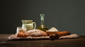 Still life photo of bread and flour with milk and eggs Royalty Free Stock Photography