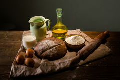 Still life photo of bread and flour with milk and eggs Royalty Free Stock Photo