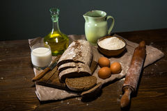 Still life photo of bread and flour with milk and eggs Stock Image