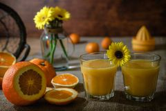 Fresh homemade orange juice with slices of oranges on a kitchen table royalty free stock photo