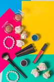 Still life photography, cosmetics to multi-colored bright background, pink, yellow, green, lipstick, lip gloss, eyeshadow, eyeline. Still life photography stock image