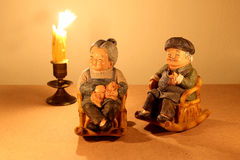 Still life photography with lovely senior couple doll siting rocking bamboo chair with light of the candle in the dark on wood bac Stock Images
