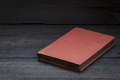 Still life photography  with old red book on wood background. Royalty Free Stock Image