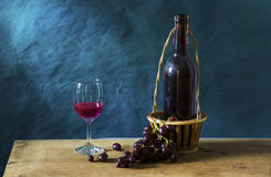 Still life Photography with Old red wine. On wooden table and blue grunge background Stock Photography