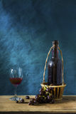 Still life Photography with Old red wine. On wooden table and blue grunge background Stock Images